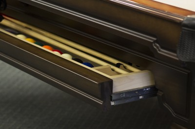 A pool table shelf to store cues and balls.